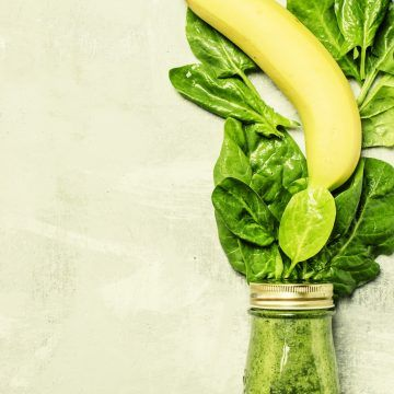 Spinach and banana green smoothies in a glass bottle, gray background