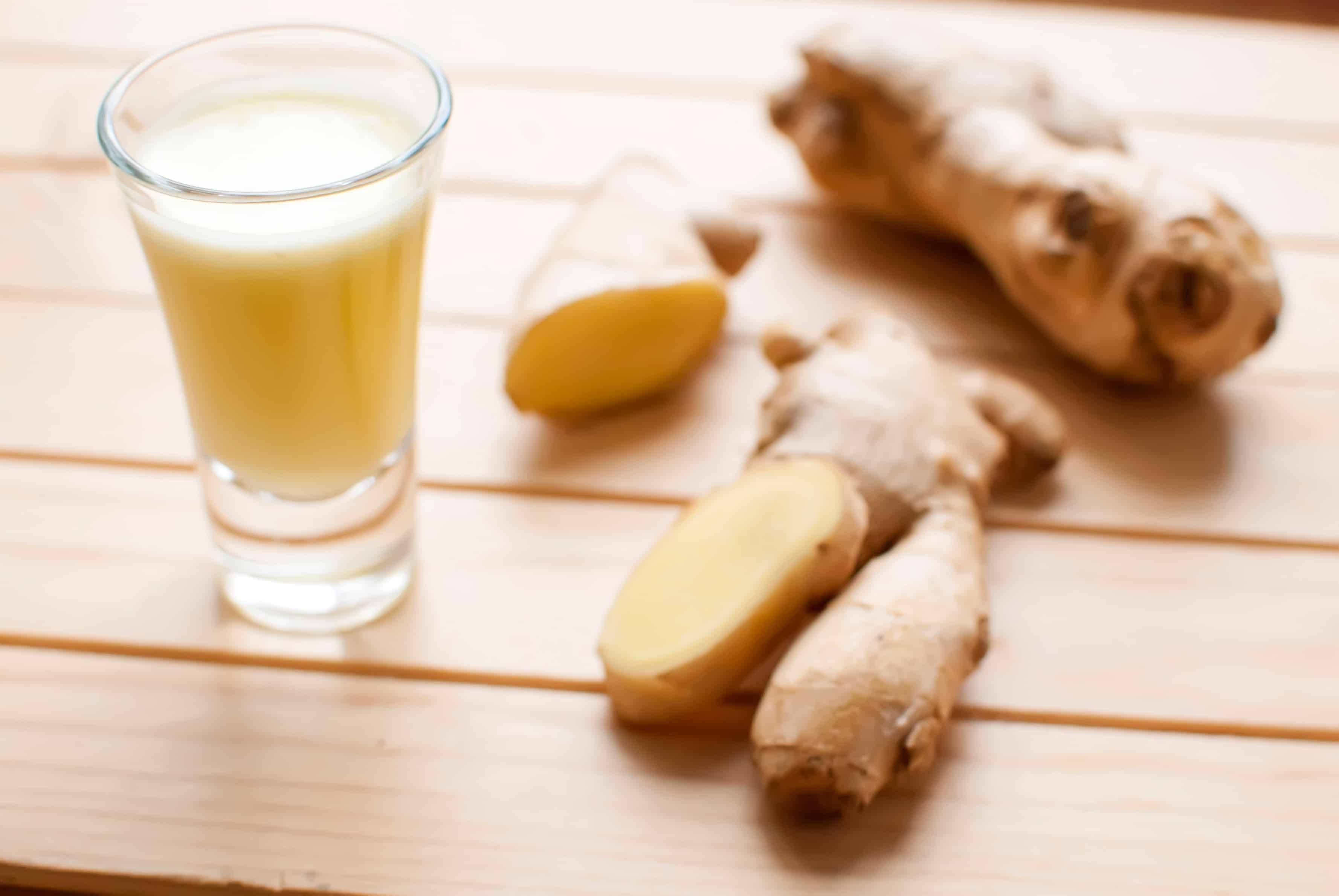 fresh organic healthy ginger shot juice and root