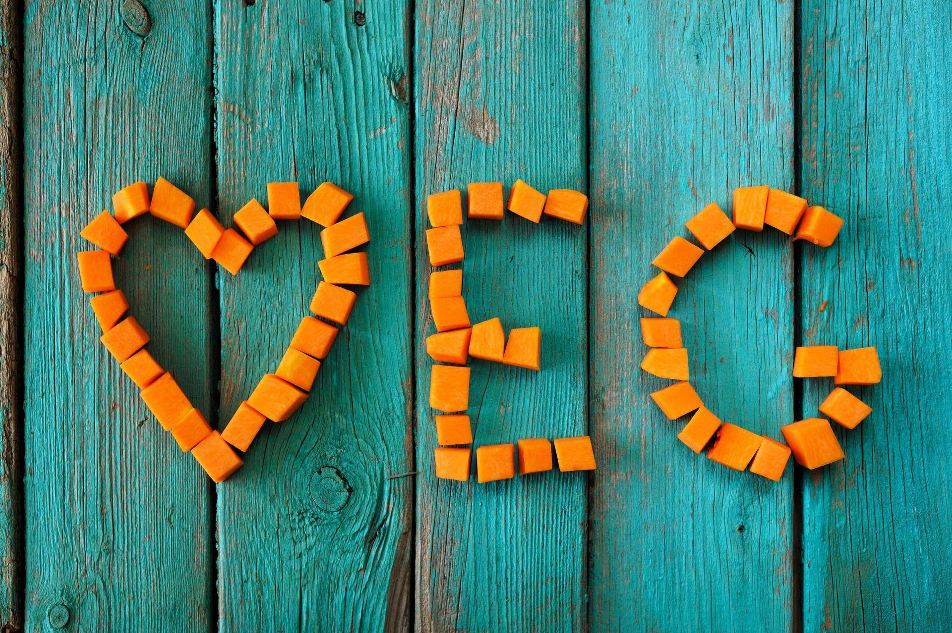 Word veg written by sweet bright pumpkin cubes on turquoise