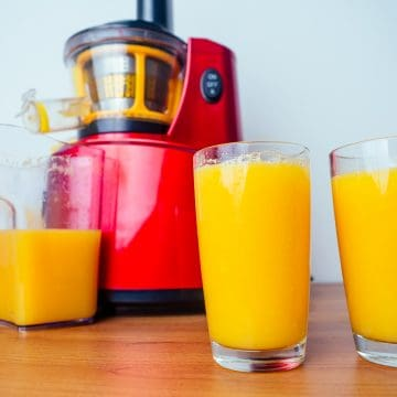 Image of a red masticating juicer on a table next to 2 glasses of orange juice