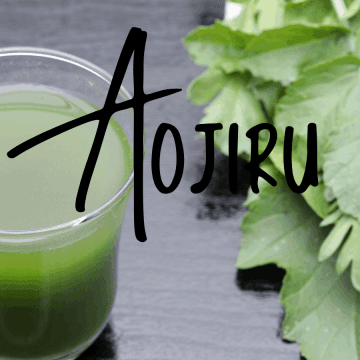 glass of aojiru juice next to green vegetables