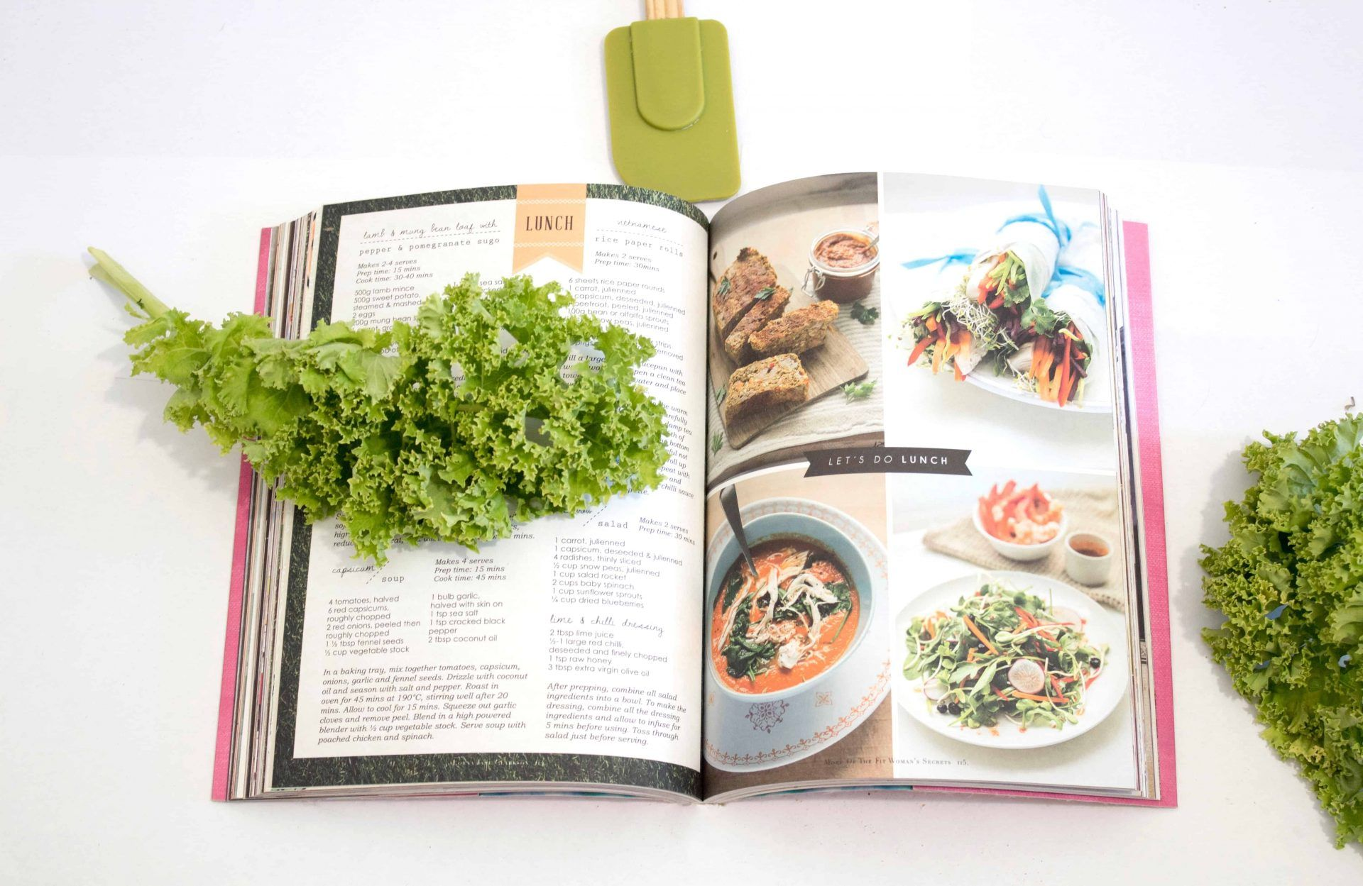 Open vegan cookbook with kale leaves and spatula next to book