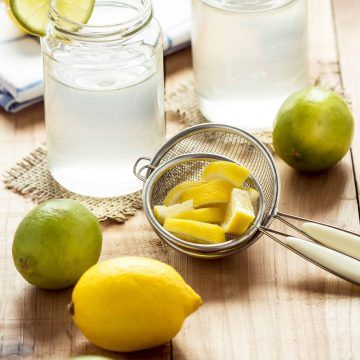 Lemons and limes on a wooden table next to a juice strainer and a glass of lemonade