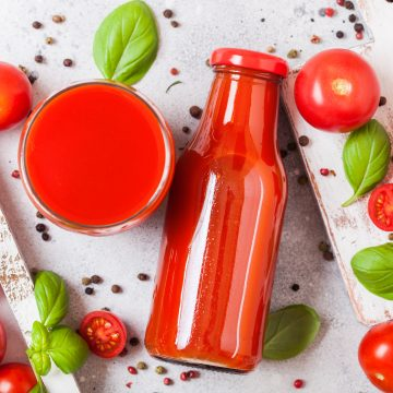 Bottle of fresh organic tomato juice with fresh tomatoes basil and pepper on a stone table