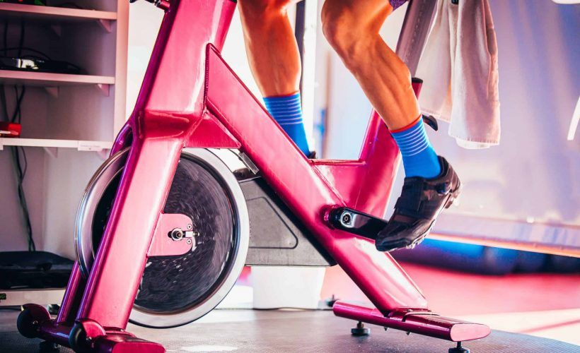 Image of a man in blue socks on a pink spin bike