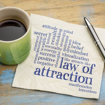 law of attraction printed on a napkin next to a cup of coffee